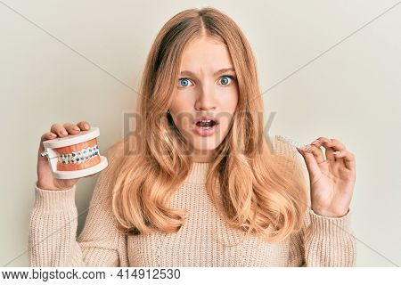 Beautiful young caucasian girl holding invisible aligner orthodontic and braces afraid and shocked with surprise and amazed expression, fear and excited face.