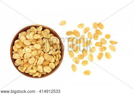 Roasted and salted fava beans for a healthy vegan and vegetarian snack in a wooden bowl on white background. Highly nutritious, high in protein, vitamins, dietary fibre and nutrients. Top view.