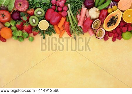 Antioxidant health food background border with fruit and vegetables high in anthocyanins, lycopene, carotenoids, vitamins, fibre, minerals and smart carbs. Immune boosting foods. On mottled yellow.