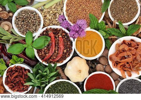 Herb and spice colorful abstract background with fresh  dried herbs and spices loose in porcelain bowls. Flat lay, top view.