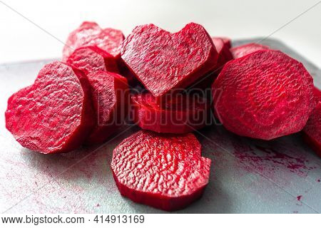 Slices of juicy beetroots in the heart shape on chopping board for cooking