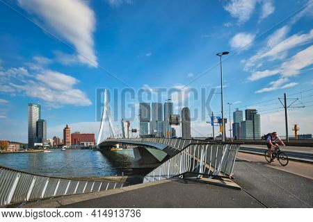 ROTTERDAM, THE NETHERLANDS - MAY 11, 2017: View of Rotterdam sityscape with Erasmusbrug bridge over Nieuwe Maas and modern architecture skyscrapers with speed boat passing uner the bridge
