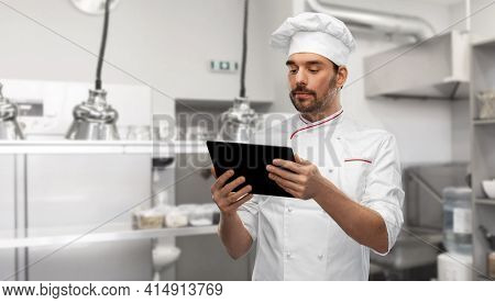 cooking, culinary and people concept - male chef in toque with tablet pc computer over restaurant kitchen background