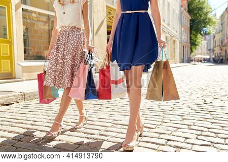 sale, consumerism and people concept - young women with shopping bags walking along city street