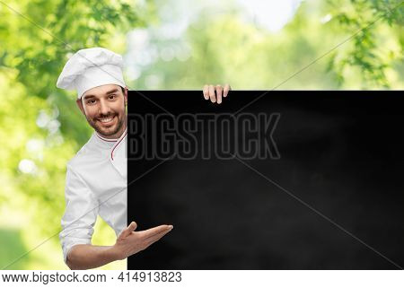 cooking, culinary and people concept - happy smiling male chef in toque with big black chalkboard white board over green natural background
