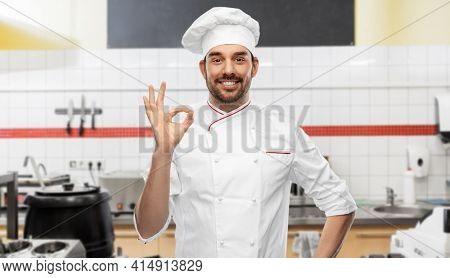 cooking, culinary and people concept - happy smiling male chef in toque showing ok hand sign over restaurant kitchen background