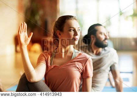 fitness, yoga and healthy lifestyle concept - woman with group of people doing half lord of the fishes pose in gym or studio