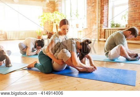 fitness, sport and healthy lifestyle concept - group of people with personal trainer doing yoga exercises on mats in gym or studio