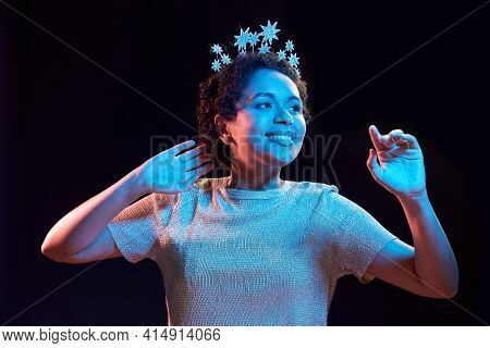 celebration and nightlife concept - happy smiling young african american woman dancing at christmas or new year party over ultraviolet neon lights on black background