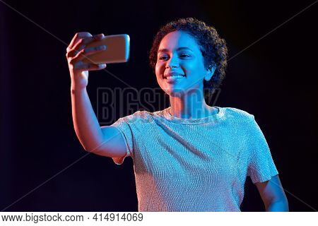 nightlife, technology and people concept - happy young african american woman taking selfie with smartphone in neon lights over black background