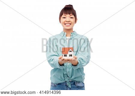 mortgage, real estate and accommodation concept - happy smiling asian woman holding house model over white background