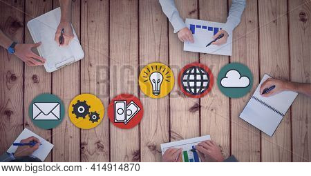 Composition of digital icons over business people making notes during meeting. global business and finance, connection and networking concept digitally generated image.