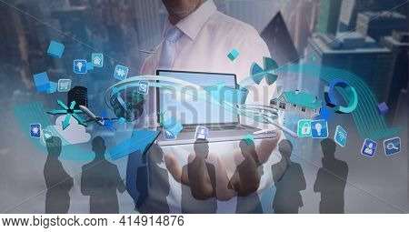 Composition of digital icons over businessman holding laptop and silhouettes of business people. global business and finance, connection and networking concept digitally generated image.