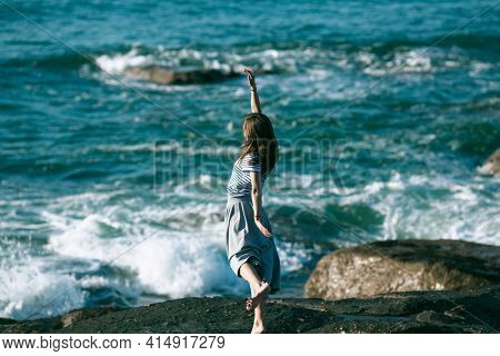 Woman dancer is engaged in choreography on the ocean coast.