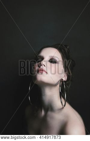 Vintage style portrait of beautiful young girl with smoky eye makeup and fancy ring earrings