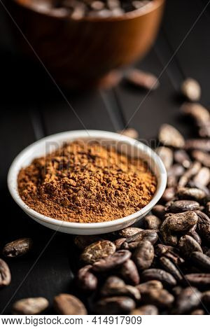 Roasted cocoa beans and cocoa powder in bowl on black table.