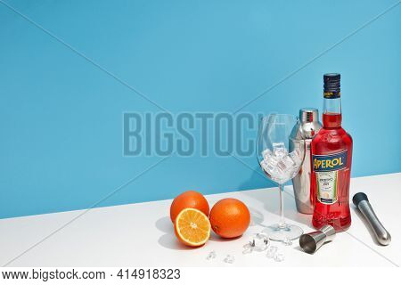 St.Petersburg, Russia - February 2021 - Bottle of Aperol aperitivo, oranges and glass with ice standing on white table on blue background. Italian bitter aperitif