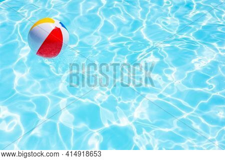Beach ball floating in swimming pool background concept for summer vacation, relaxation and fun in the sunshine