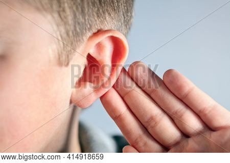 Child with hand on ear listening for quiet sound or paying attention