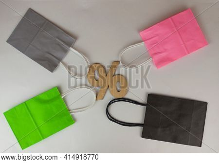 Top view. Colorful paper shopping bags on the white background. Sale, consumerism, advertisement and retail concept
