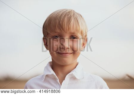 Face close - up of a boy of eight years. Portrait of a smiling boy in nature looking at the camera. Happy blond boy with a smile on his face. Child in a white shirt with blue eyes in nature.