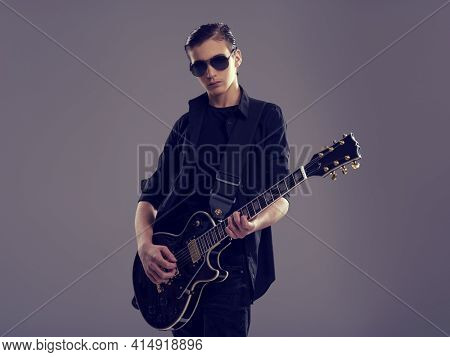 Fifteen years old guitarist with a  black electric guitar. Teenage musician holds guitar, posing at studio. The young caucasian guy with a guitar. Boy's playing rock music. Heavy metal player.