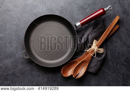 Frying pan and utensils on kitchen table. Top view flat lay with copy space