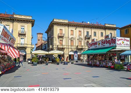 ALBA, ITALY - MARCH 13, 2021: Mobile stalls sell torrone and other traditional sweets on piazza Ferrero in Alba - small town in Piedmont region, famous for white truffles and wine production.