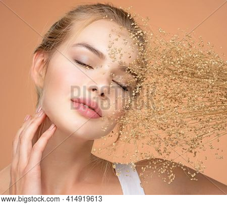 Calm Blonde girl with a bunch spring dry field flowers near the face - over colored background. Beauty face care concept. Young beautiful serene woman with a healthy  skin of the face, closed eyes.
