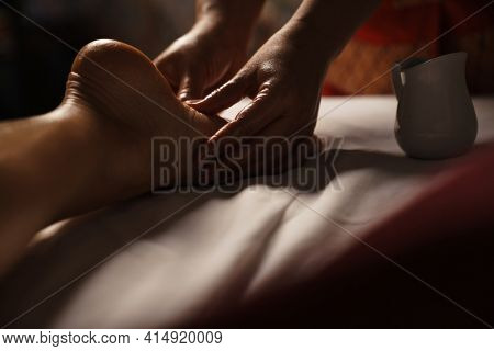 Professional masseuse doing foot massage with oil in spa indoors