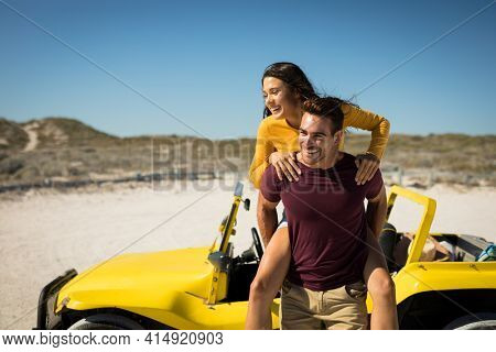 Happy caucasian couple next to beach buggy by the sea piggybacking. beach break on summer holiday road trip.