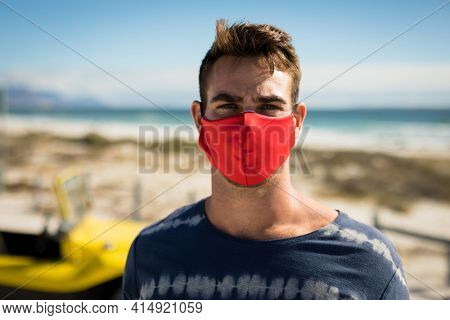 Portrait of happy caucasian man wearing face mask next to beach buggy looking to camera. beach stop off on summer holiday road trip during coronavirus covid 19 pandemic.