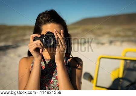 Caucasian woman next to beach buggy by the sea taking picture. beach break on summer holiday road trip.