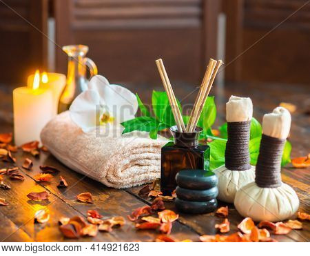 Spa background. Towel, candles, flowers, aroma sticks, massaging stones and herbal balls. Massage, oriental therapy, wellbeing and meditation.