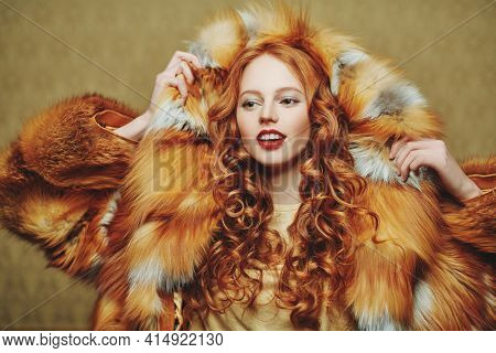 Beautiful young woman with red hair poses in a luxurious fox fur coat on a light brown vintage background. Winter beauty fashion. Fur coat style.