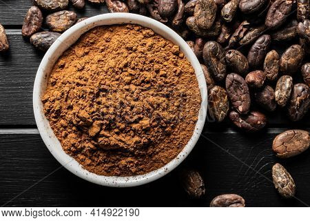 Roasted cocoa beans and cocoa powder in bowl on black table. Top view.