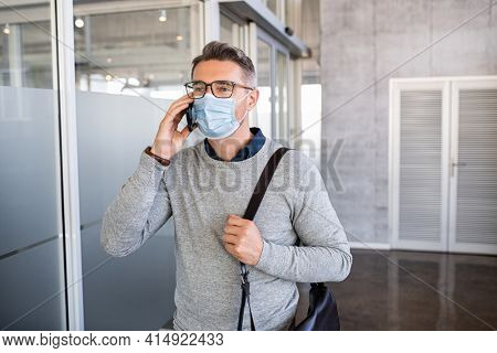 Mature casual businessman talking over phone while wearing surgical face mask during covid pandemic. Successful business man wearing face mask protecting himself from coronavirus in office.