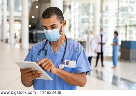 Middle eastern nurse using digital tablet while wearing surgical mask. Busy doctor working on digital tablet and wearing protective face mask for coronavirus safety. Healthcare indian worker in clinic
