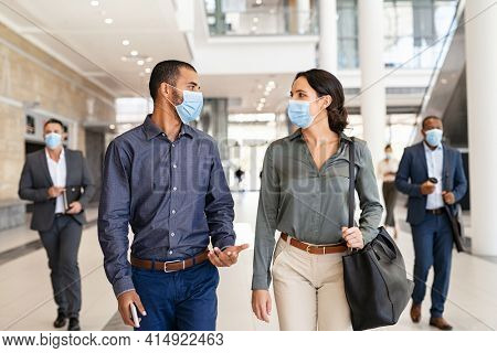 Indian business man and businesswoman walking with face mask and talking at modern workspace. Two colleagues wearing protective mask due to covid-19 while going to work, new normal concept.