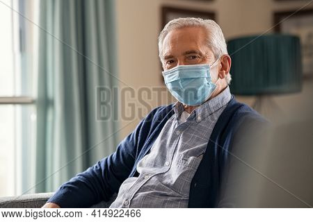 Portrait of smiling old man wearing surgical face maskfor safety against covid-19 at nursing home. Senior man with face mask sitting on sofa at home during lockdown due to covid. Happy elder at home.