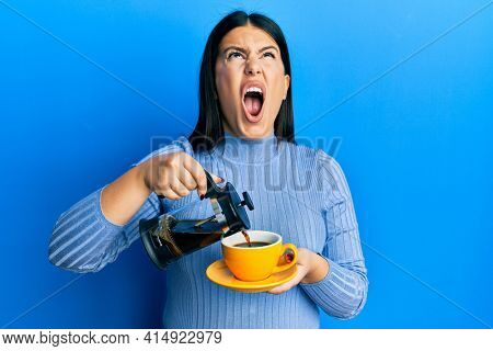 Beautiful brunette woman holding french coffee maker pouring coffee on cup angry and mad screaming frustrated and furious, shouting with anger looking up.
