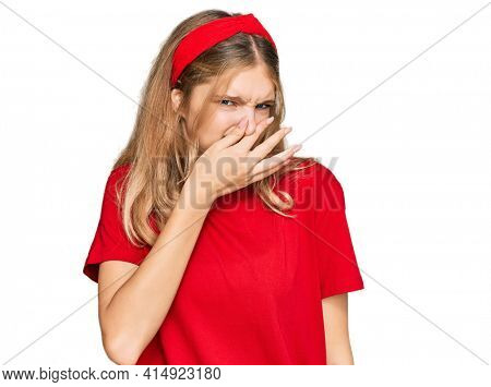 Beautiful young caucasian girl wearing casual red t shirt smelling something stinky and disgusting, intolerable smell, holding breath with fingers on nose. bad smell