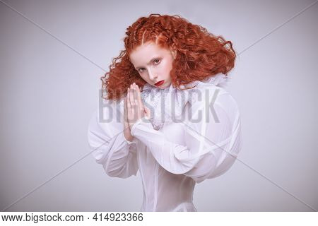Female model with lush red curly hair posing in a white art dress. A studio portrait on a light grey background.