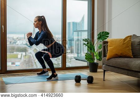 Slender brunette in turquoise jumpsuit with brown ponytail hair in squat position near panoramic window on glazed balcony