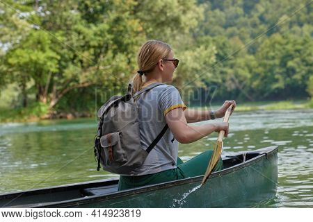 woman adventurous explorer are canoeing in a wild river