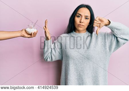 Young hispanic girl rejecting bowl with sugar with angry face, negative sign showing dislike with thumbs down, rejection concept