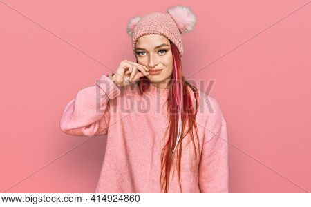 Young caucasian woman wearing casual clothes and wool cap mouth and lips shut as zip with fingers. secret and silent, taboo talking