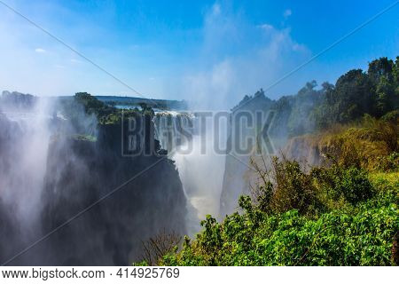 Giant cloud of mist rose above the waterfall. Journey after the wet season. Dizzy Victoria Falls. The waterfall is located on the Zambezi River. Concept of extreme and photo tourism