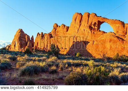 Picturesque red-brown sandstone cliffs form a unique landscape. Skyline Arch. The unique beauty of Arches Park in USA. Grandiose rock compositions natural origin