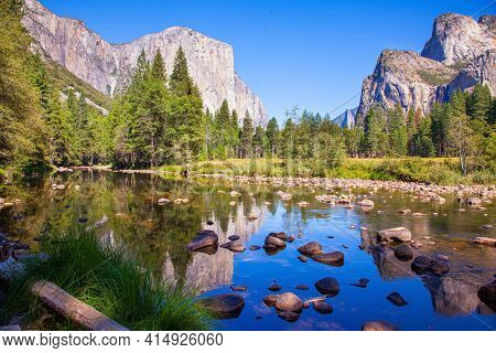 Beautiful day in the park valley. Yosemite Park is located on the slopes of the Sierra Nevada. Charming El Capitan and trees is reflected in the smooth water of little lake